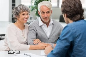 Orange County estate planning attorney - Senior couple meeting real estate agent. Senior couple meeting financial advisor for investment. Happy mature man and woman listening to various investment plans for their retirement.