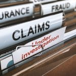 Los Angeles business litigation lawyer - Folder with close up on the word claims and a note where it is written under investigation. Concept of insurance fraud 3d Illustration